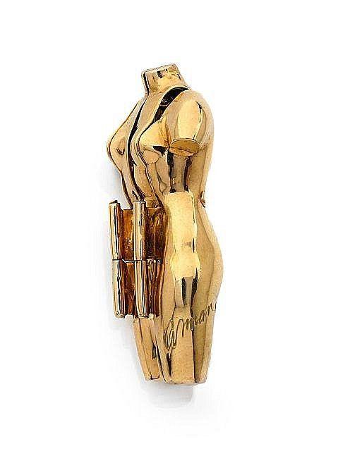 """<b>ARMAN</b> (1928-2005) <br /> <b>Broche """"Vénus inter-active""""</b> <br /> En or jaune 18k (750), stylisée d'un corps féminin s'ouvrant par des charnières et découvrant un violon découpé <br /> Vers 1997 <br /> Signée Arman EA 2/4 <br /> Haut: 4.5 cm, Larg.: 4 cm, Poids brut: 24.19 g <br />  <br /> Cette oeuvre est enregistrée dans les archives du Studio Arman à New York sous le numéro: APA#7041.97.006 <br />  <br /> A 18k yellow gold brooch, by Arman, circa 1997 <br /> <br />  <br />  <br />"""
