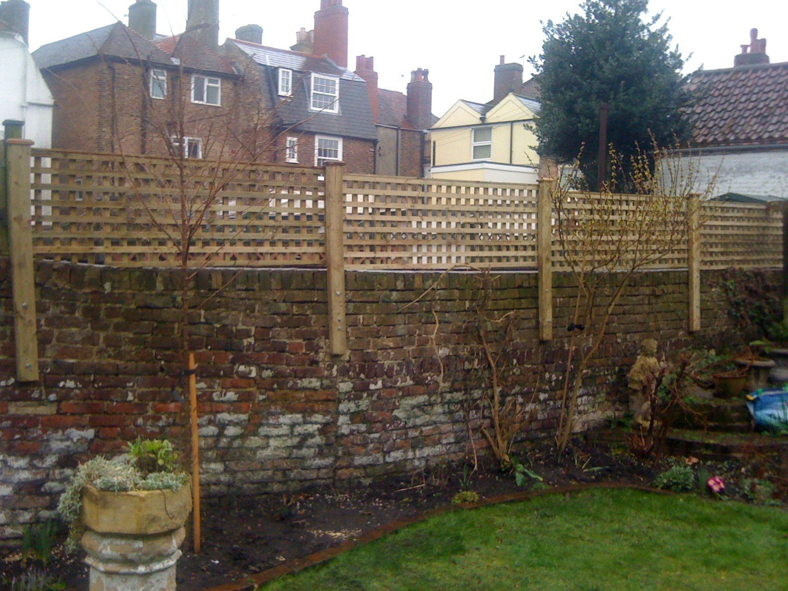 Wooden privacy trellis attached to top of brick wall ...