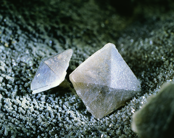 These prominent smoke-grey bipyramids are crystals of stolzite, originating from Broken Hill, far-western NSW. The largest crystal is only 3mm long on its longest edge. Stolzite is a lead tungsten mineral (PbWO4), while pyromorphite is a complex species of lead chlorophosphate. Broken Hill has produced some of the finest specimens of stolzite known. DPI Economic Rock & Mineral Collection specimen No. 5153. Photographer - David Barnes. http://www.trade.nsw.gov.au/legal/copyright