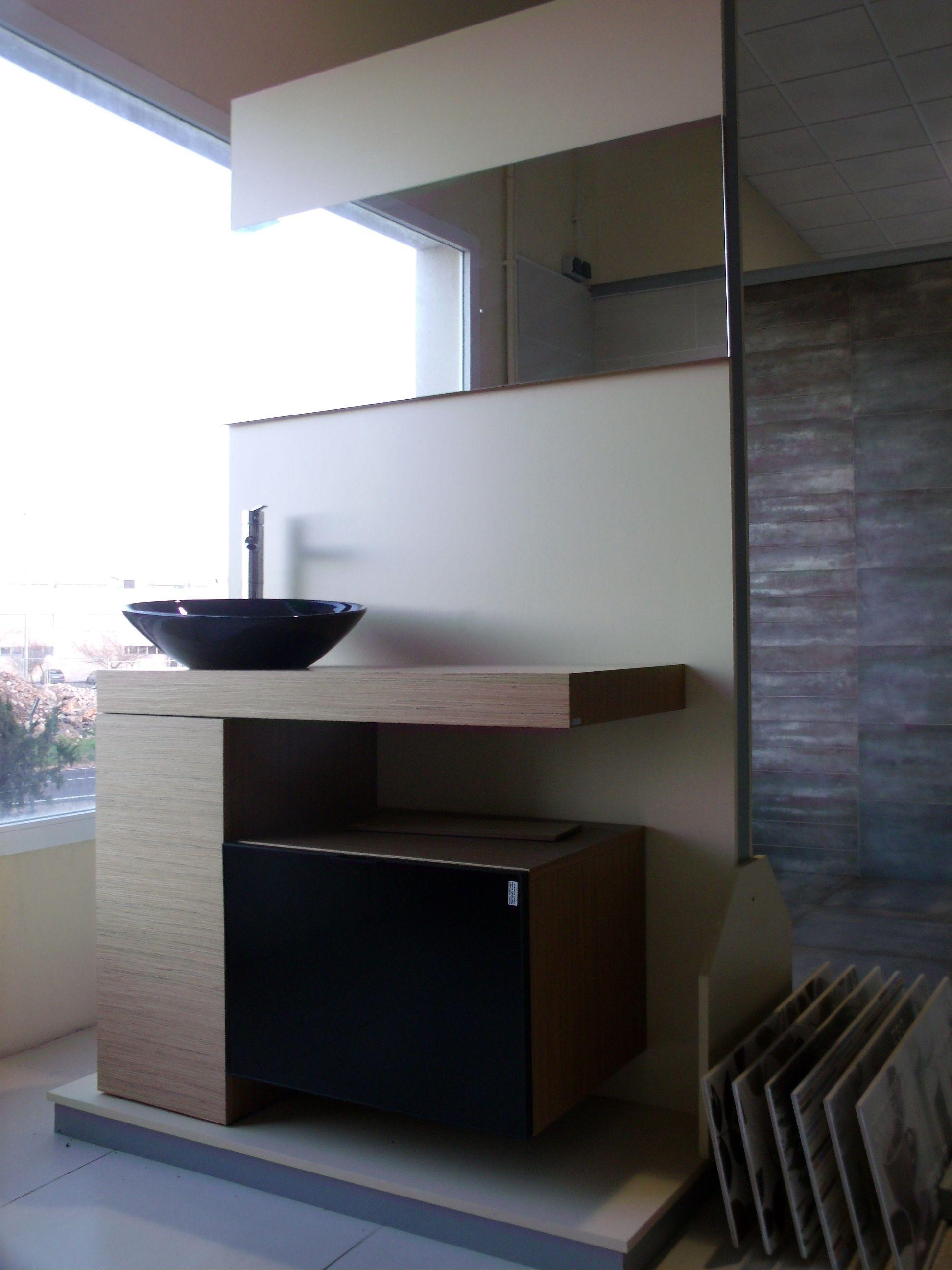Mueble de baño compuesto por un lavabo negro en forma de cuenco ...
