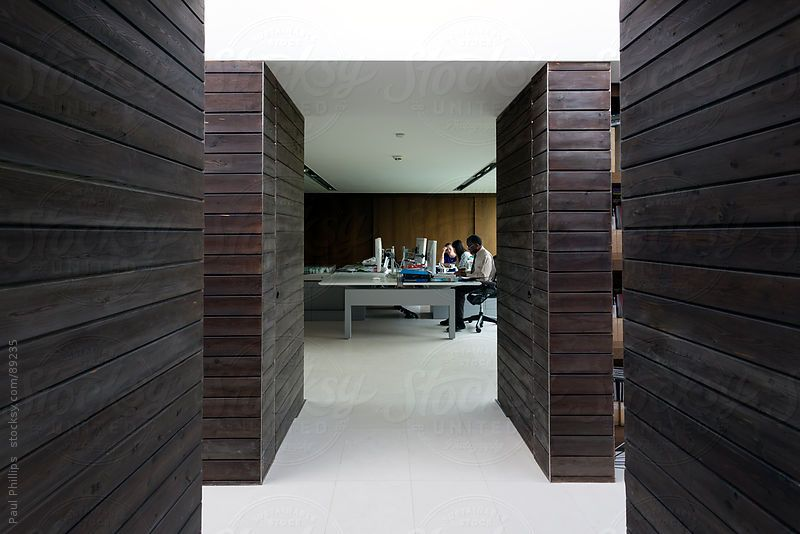 Internal wooden partitions in a modern office with  corridor leading to office. Three people collaborating in office.