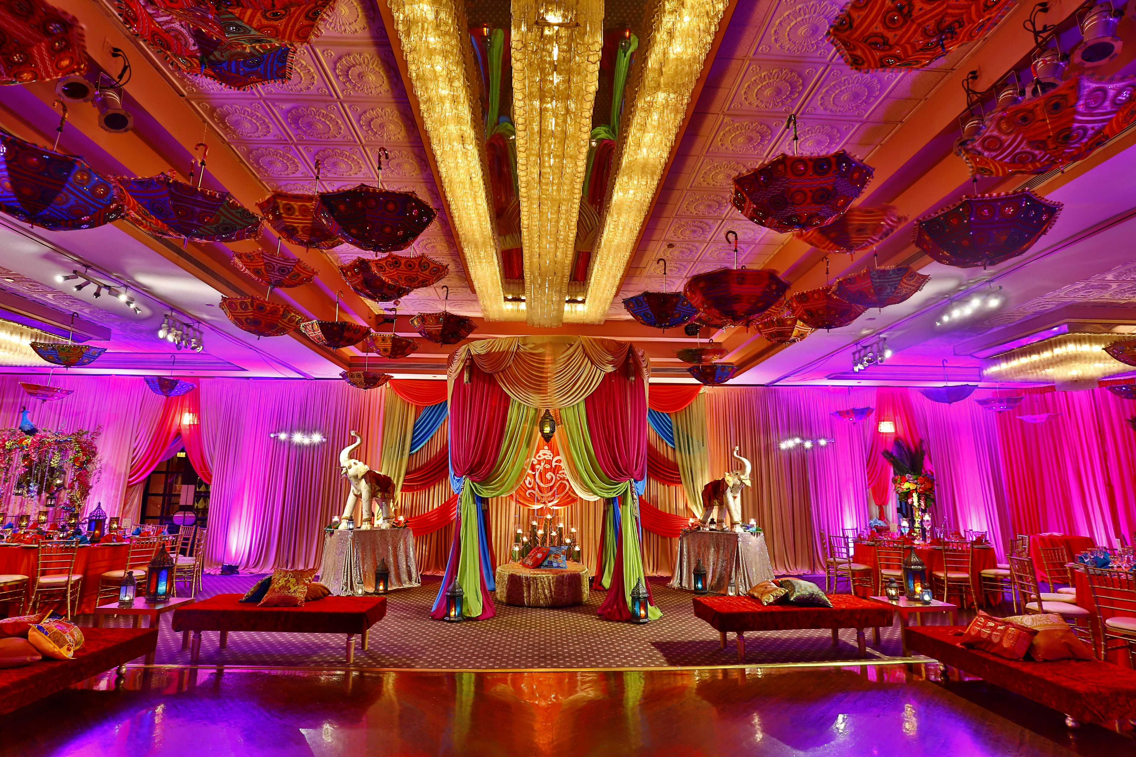 b42f80f98be93 #Exquisite #Indian #wedding #reception #decor featuring #LED #light  fixtures, #colorful #drapery with #elephant #centerpieces and #umbrellas