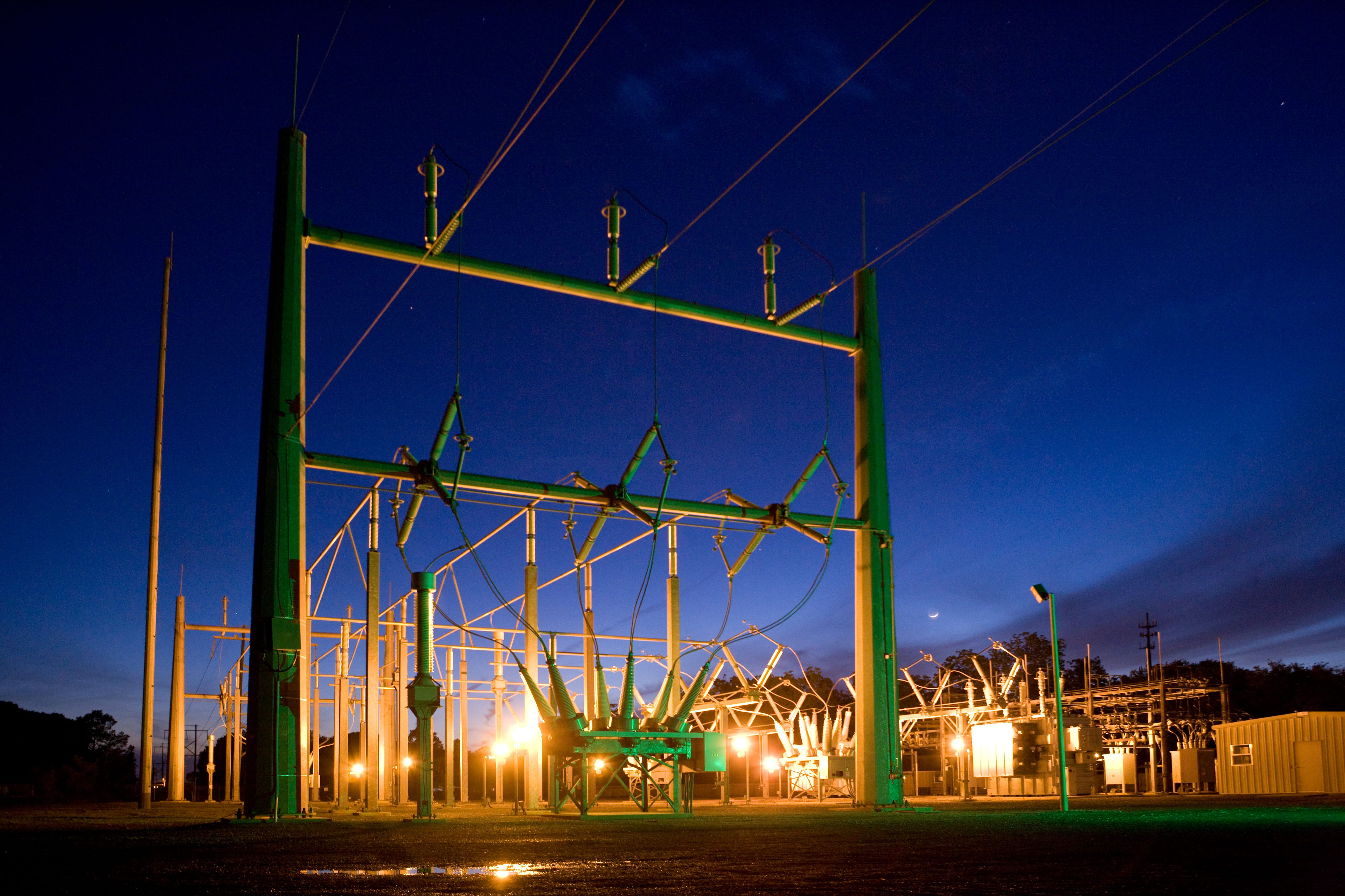 green and grey transmission tower during nighttime, green