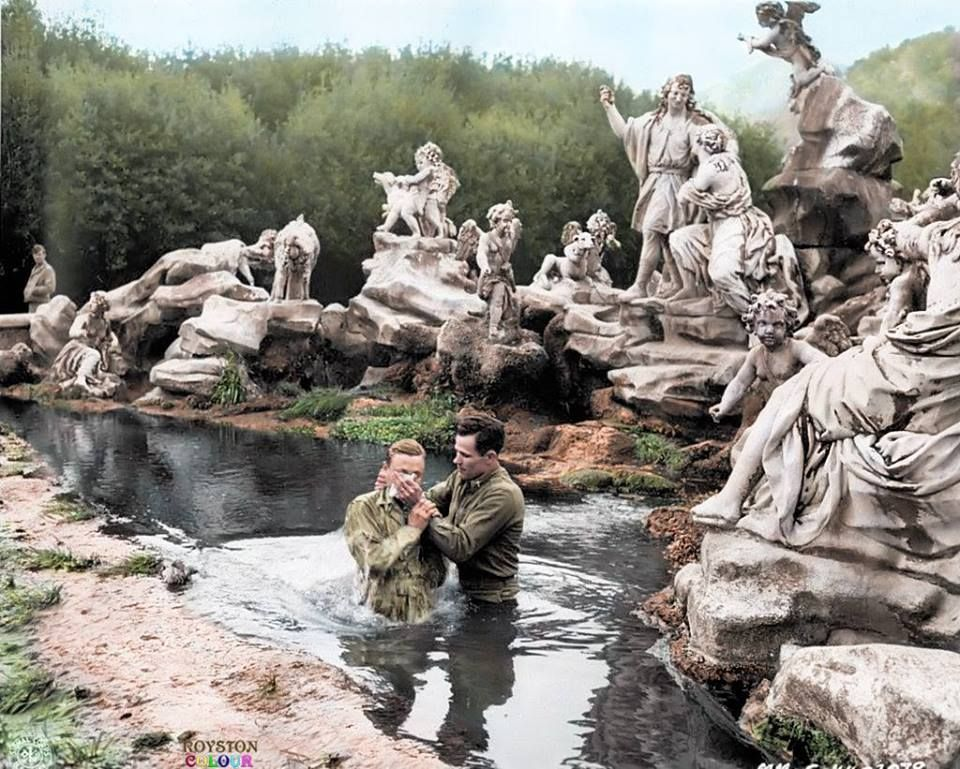 A US Army Chaplain baptizes a Corporal in the Venus and Adonis Fountain at the Royal Park of the Palace of Caserta in Southern Italy. 1943/44