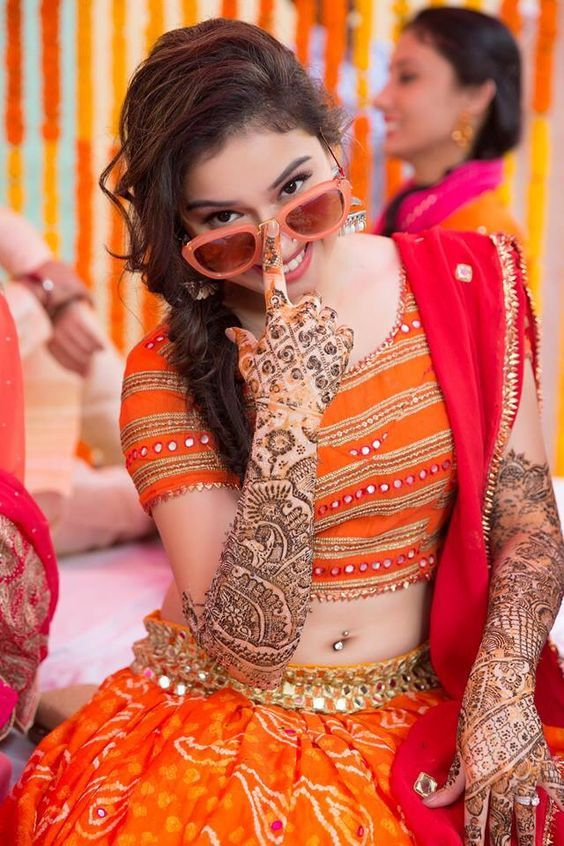 Beautiful bride in bright orange lehenga with red dupatta | lehenga with mirror work | Stunning mehndi outfit inspiration for Indian brides | Bride in Quirky sunglasses | Bridal swag | Credits: Aditi Oberoi Photography | Every Indian bride's Fav. Wedding E-magazine to read. Here for any marriage advice you need | www.wittyvows.com shares things no one tells brides, covers real weddings, ideas, inspirations, design trends and the right vendors, candid photographers etc.