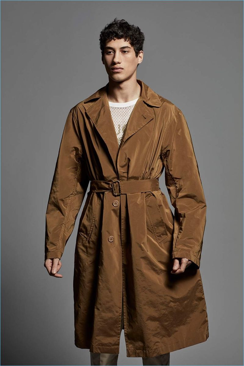Malik Al Jerrari wears a Dries Van Noten trench coat with a Gucci mesh  t-shirt and AMI trousers. a0a9bff51