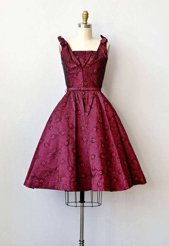 vintage 1950s red bombshell party dress  Name:Holiday Kiss Dress    Stunning bombshell dress in dark crimson red with black feathery floral print. Pleated bust on the bodice, ties on the shoulders, and full swing skirt (worn with petticoat for added fullness). Comes with original belt. Side metal zipper.