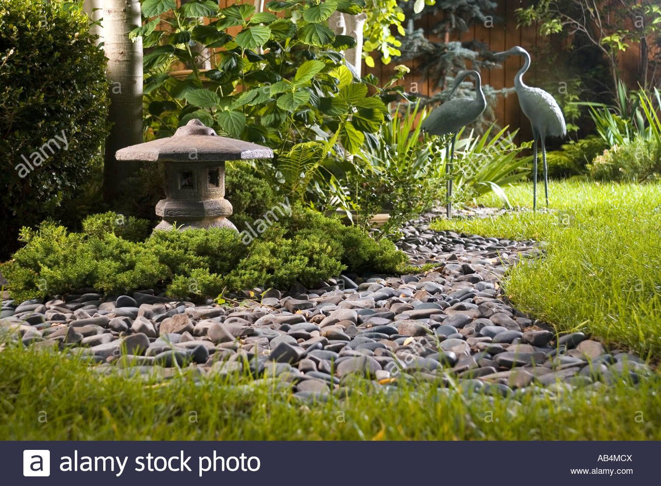garden cranes. Stock Photo Titled: A Backyard Japanese Garden With Dry Stream Bed, Lantern And Crane Statuary, Unlicensed Use Prohibited Cranes