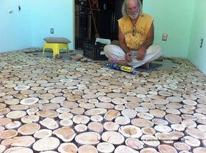 Il se construit un sol magnifique avec des rondelles de bois de chauffage ! Une idée de génie !