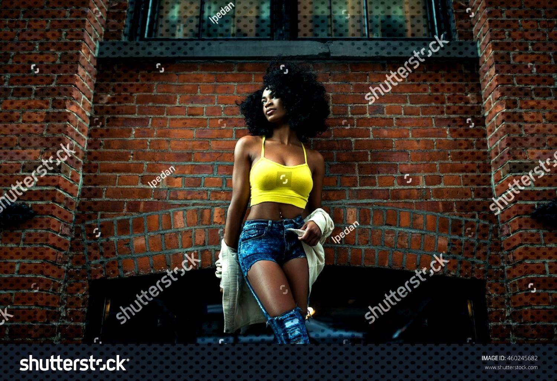 Fashion shot of beautiful afro american girl in vintage Brooklyn bridge park\n ,