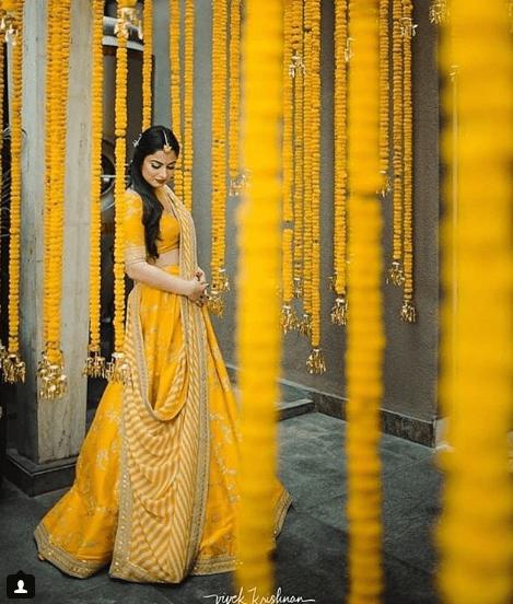 5401df954c Bride in yellow on haldi | Marigold flower chains with kaleere | Haldi decor  ideas | Sabyasachi Yellow lehenga | Bridal photoshoot ideas | Bridal  portrait ...