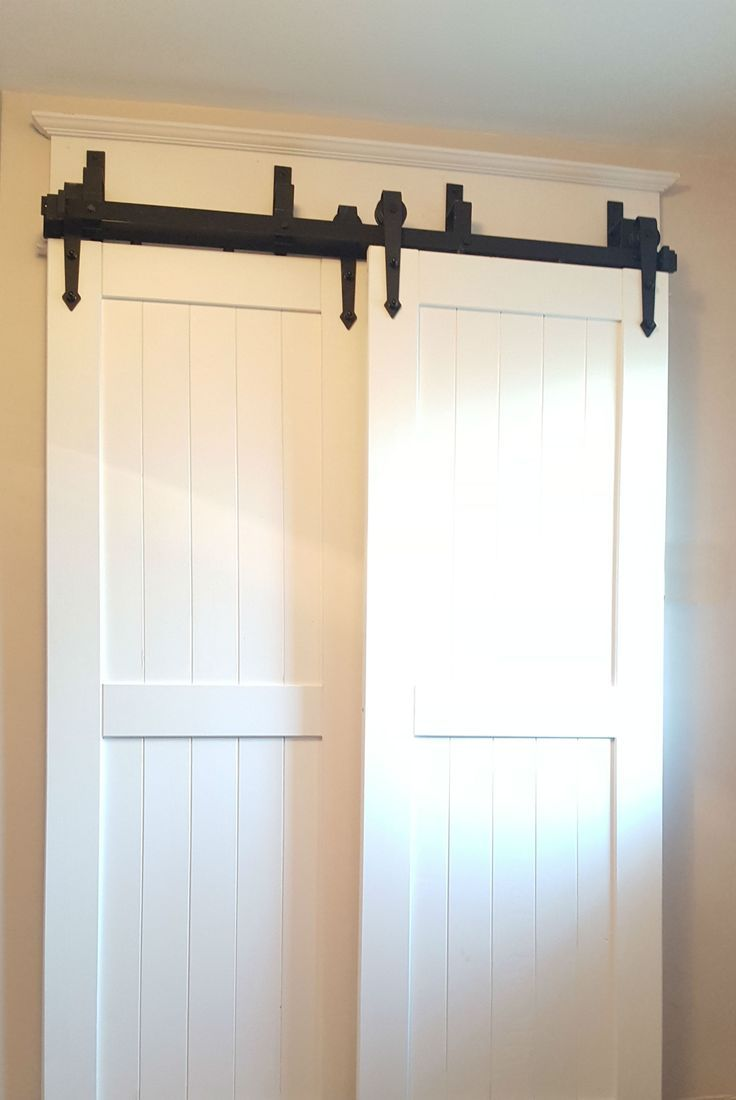 The Raised Panels On These White Barn Doors With The Contrasting Hardware Gives A Classic Look To T Bypass Barn Door Bypass Barn Door Hardware Barn Door Closet
