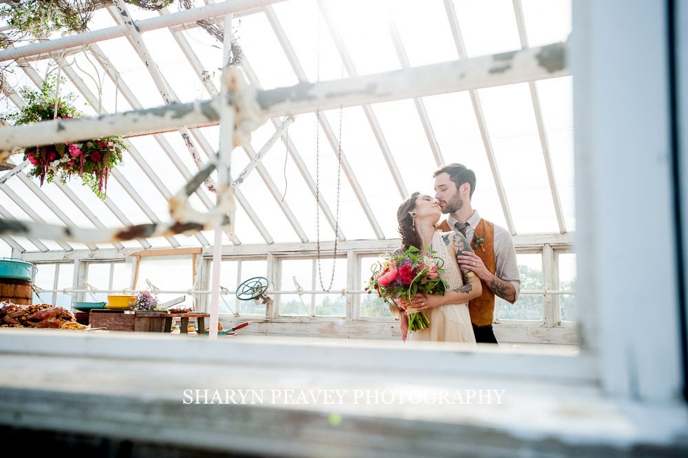 bride and groom portrait in greenhouse, red and pink bouquet