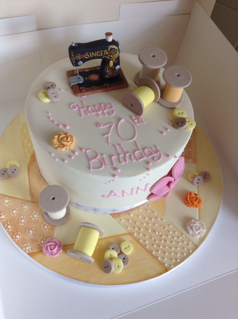 A patchwork sewing theme cake topped with a singer sewing machine cake topper