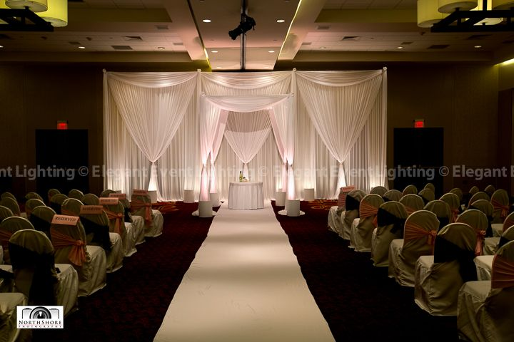 Renee Kris Ceremony Décor Began With A White Fabric Backdrop That Was Bathed In Soft Lighting