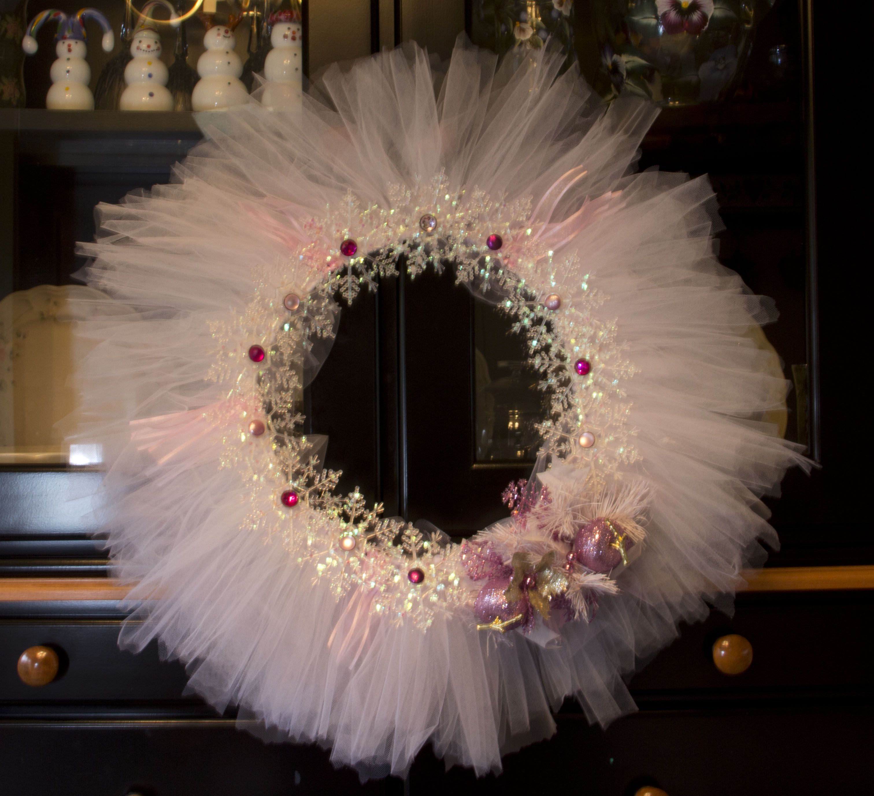 To start your Christmas tulle wreath, you will need to cut your tulle into strips. Have someone help you by holding the tulle, it makes it way easier to cut!