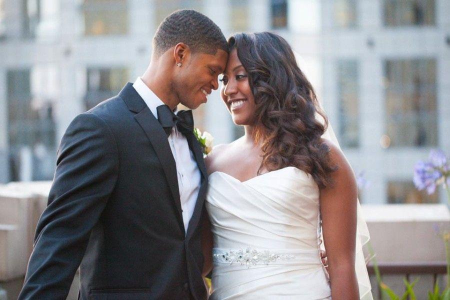 Noivo negro com terno preto e gravata borboleta preta, com sua noiva negra…