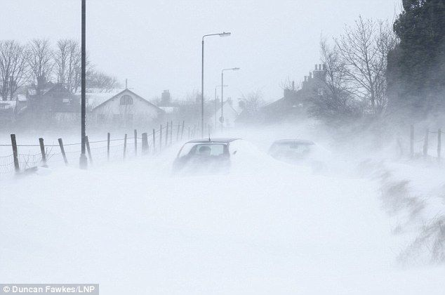 Whiteout: Blizzards caused huge snow drifts leaving these cars nearly completely covered in Hadfield, Derbyshire