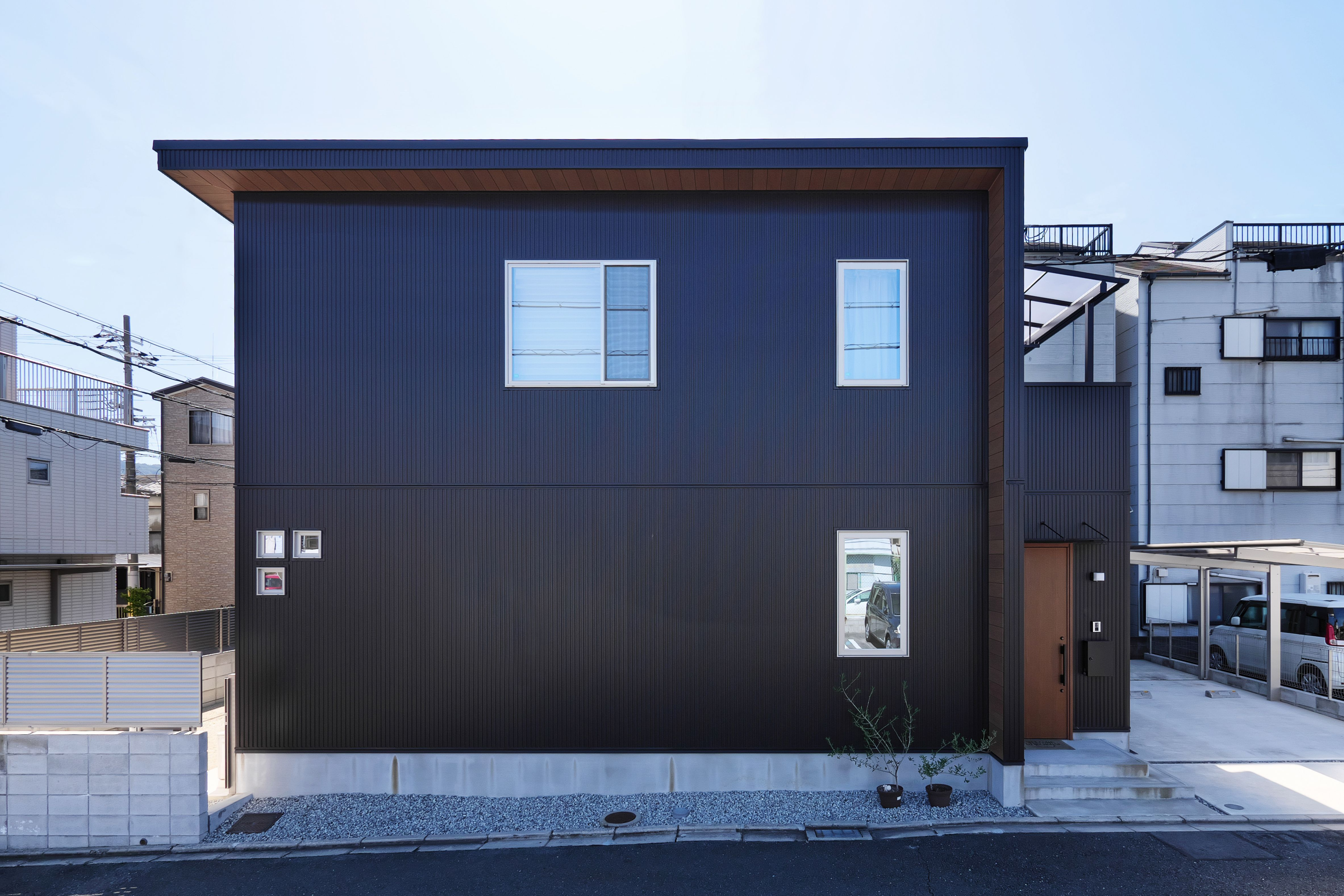 シンプルなキューブ型の外観に木調サイディングを施したl字型の軒が