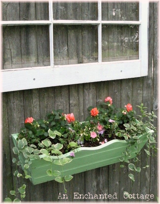Old window hanging from wood fence with window box planter