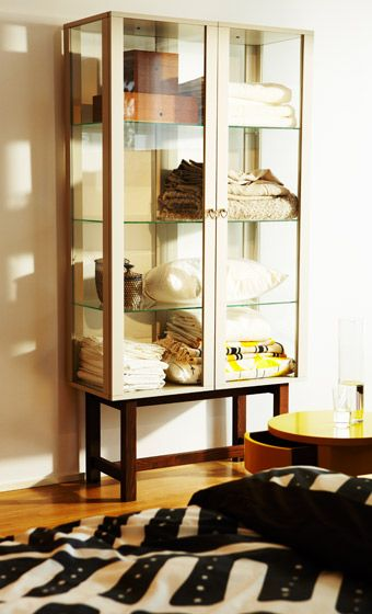 Stockholm Glass Door Cabinet In Beige Filled With Bed Linen By Ikea