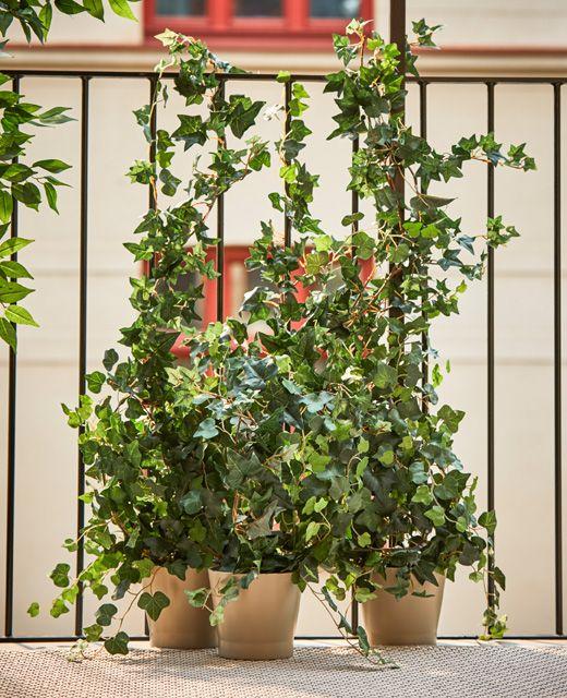 Las plantas artificiales puestas en macetas alrededor de for Decoracion jardin macetas