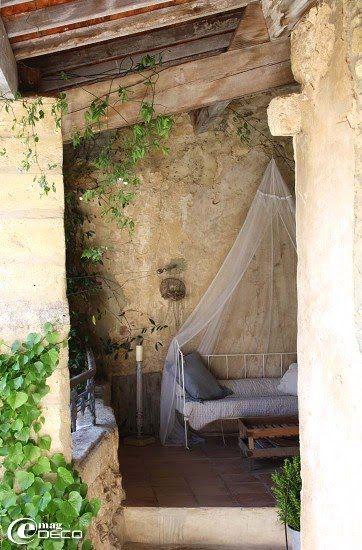 La terrasse couverte, son lit en fer forgé coiffé d\u0027une moustiquaire