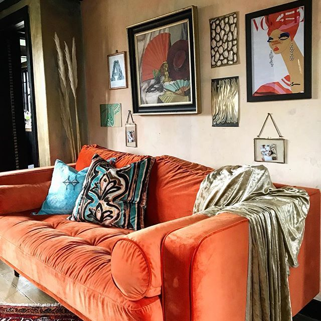 Stunning burnt orange velvet sofa - a snap from Anna Hayman's house tour organised by Decorcafe - note the Anna Hayman fabric cushions which really standout against the orange#annahaymandesigns #decorcafe #burntorangesofa #velvetvintagesofa