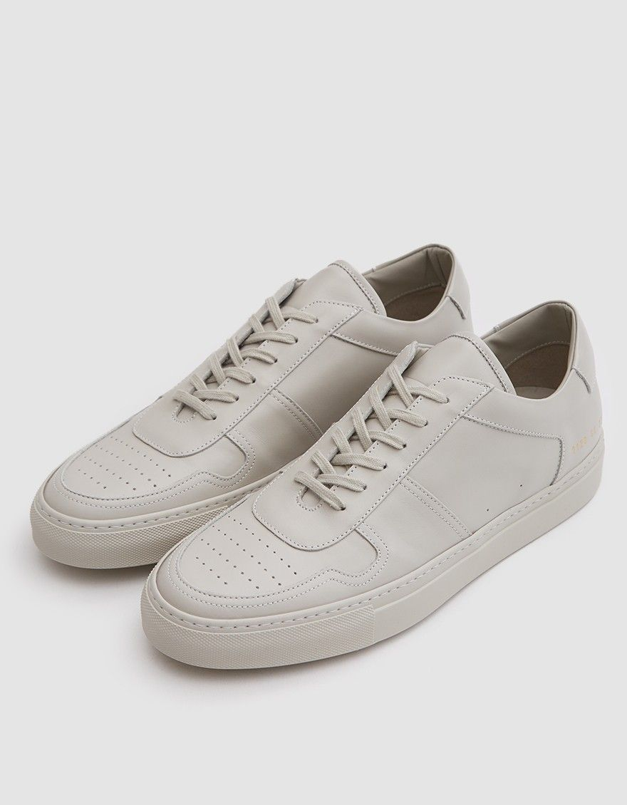 791e63f5ef56 Premium low top sneaker from Common Projects in Carta. Lace-up front with  flat woven laces. Lightly padded tongue and collar. Heat pressed gold  serial ...