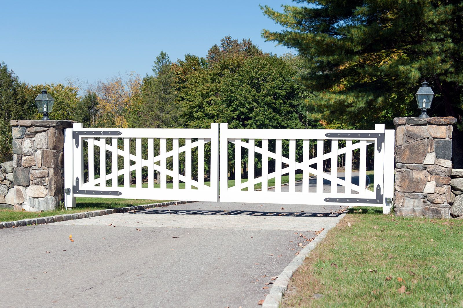 Streamlined Farmhouse Design For This White Wooden Driveway Gate Beautiful Black Iron Details And Custom Ston Farm Gate Farm Gate Entrance Wood Gates Driveway