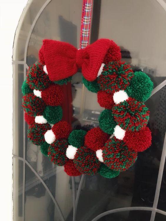 Photo of ein Weihnachtskranz aus weißen, grünen und roten Bommeln und einer Strickschle…