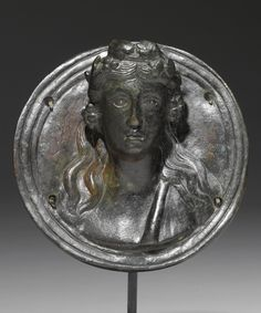 A ROMAN BRONZE ROUNDEL WITH RELIEF BUST OF DIONYSOS, CIRCA 2ND CENTURY A.D.
