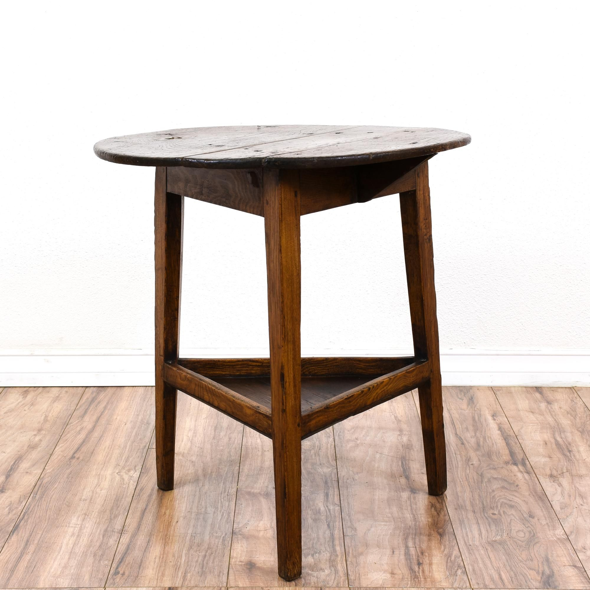 This rustic 2 tiered end table is featured in a solid wood with a distressed oak finish this farmhouse chic side table is in good condition with a round