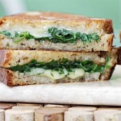 Grilled Cheese with garlic confit and arugula      8 thin slices rye country bread      1/4 cup oil from garlic confit      4 ounces baby arugula      Sea salt and freshly ground black pepper, to taste      1/2 cup garlic confit*      8 ounces aged Cheddar, Gruyère, fontina or manchego, grated coarsely