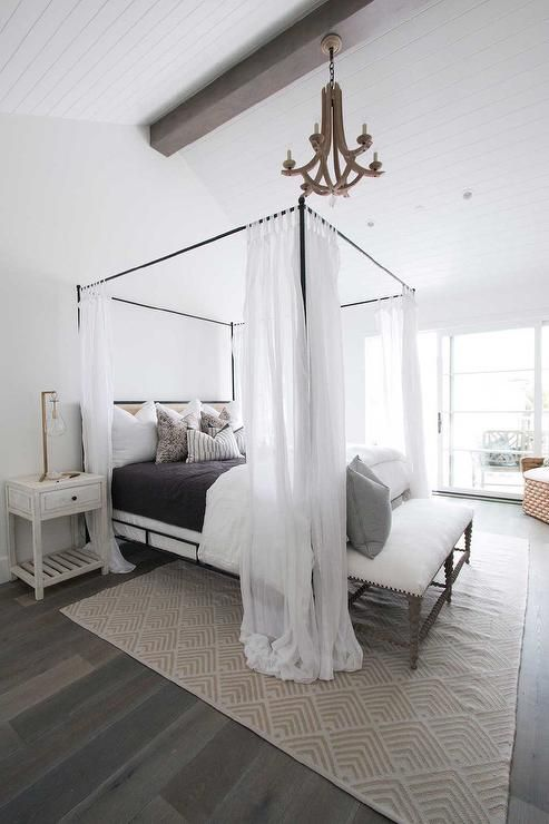 Beautiful Cottage Bedroom Features A Arteriors Manning Chandelier Hanging Over An Iron Canopy