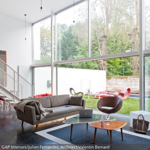 Dieses moderne Wohnzimmer mit großer Fensterfront ist eine wahre