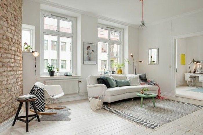 Soggiorno classico con un divano di colore bianco e parete con mattoni in vista