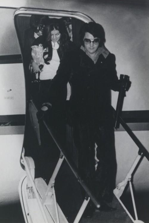Elvis - getting off the plane with flashlight in hand.