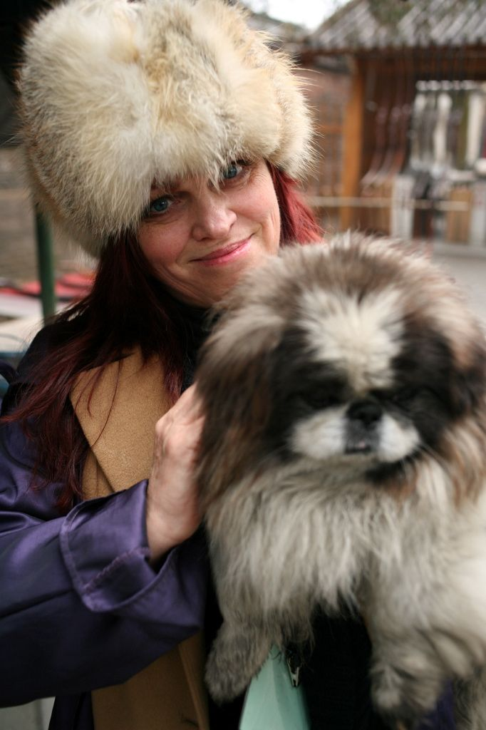 Uriél Dana with Temple Dog in China. It was so cold I was wearing  thermals, two sweaters, two pair of socks, a winter coat with a raincoat on top. I fell in love with this dog that belonged to two street painters.