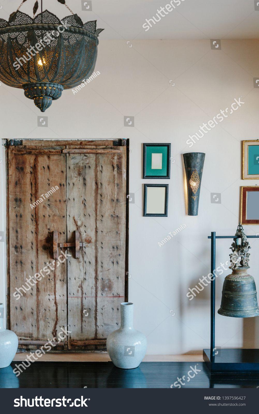 Photo of Old style interior details in luxury interior. Wooden door, big lamp, bell, pict…
