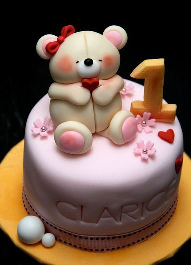 Cute round pink first birthday cake with teddy bear on topJPG