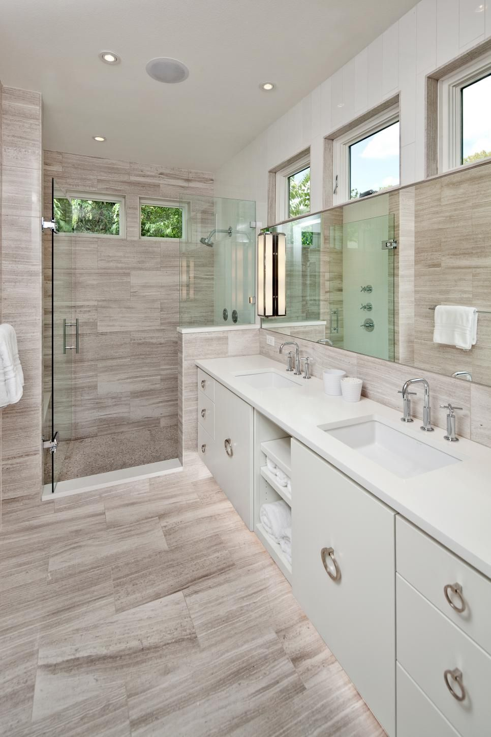 Gray wood look tile for the walls and floors crisply contrasts the white vanity in this spa Bathroom design spa look
