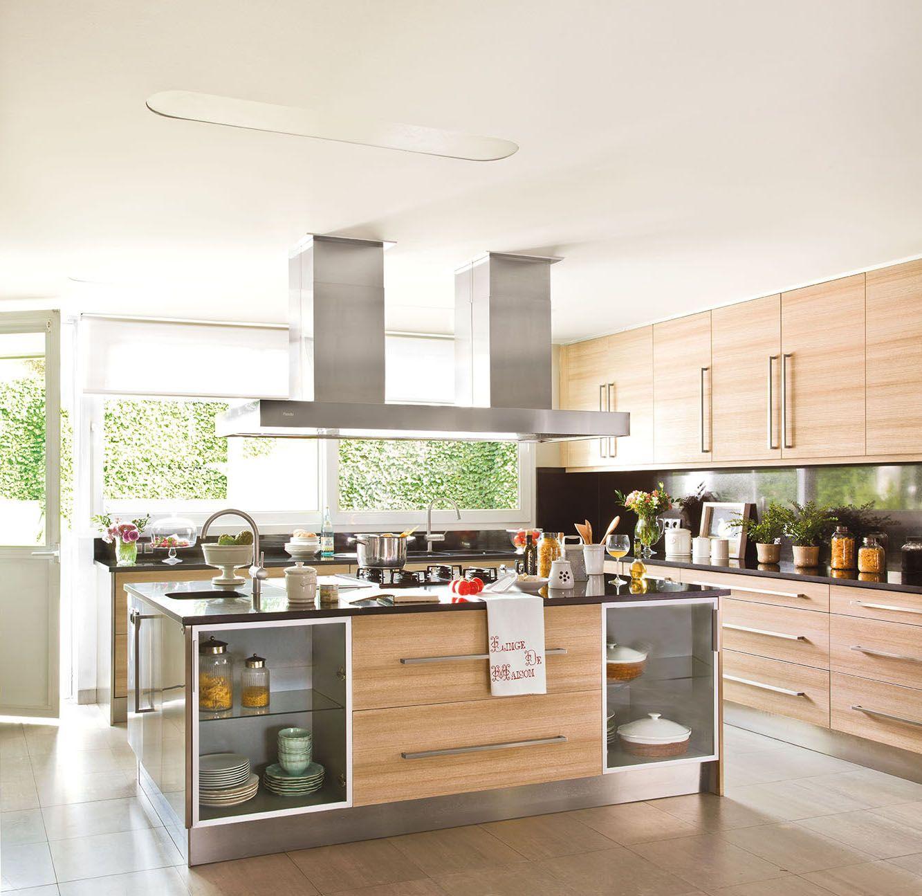 Cocina con muebles de madera clara y encimera negra e isla con dos campanas c5ca5d485a6e