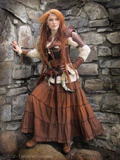 Viking woman. Poet's Shirt. Underbust vest. Bracer. Pauldron. Drinking horn. Thick belt. Old key. Leather boots. Skirt.