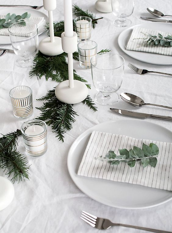 a minimalist table setting with an evergreen garland, white candles ...