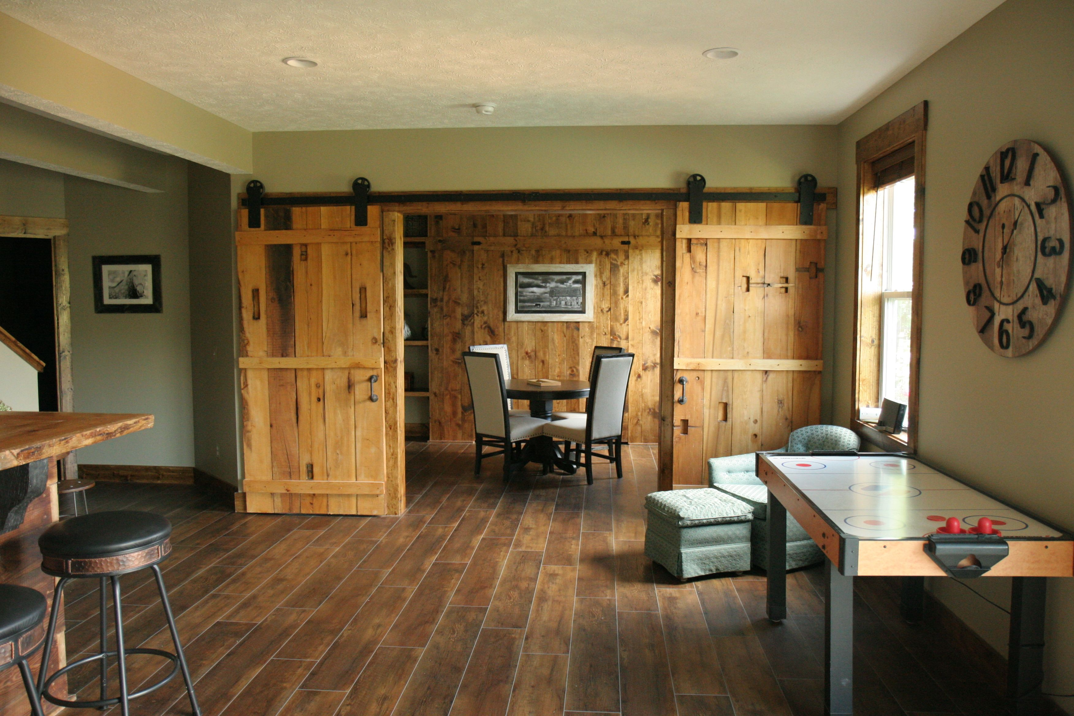 Basement game room with sliding barn doors and murphy bed behind