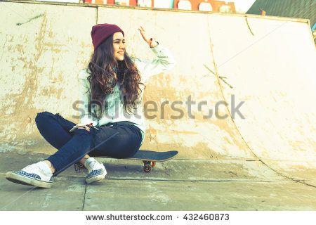 Awesome skateboarder girl with skateboard outdoor sitting at skatepark. Vintage image. Old school. Skatebord at city street. Cool, Funny Tenager. Half-pipe. Skateboarding at Summer. Schoolgirl