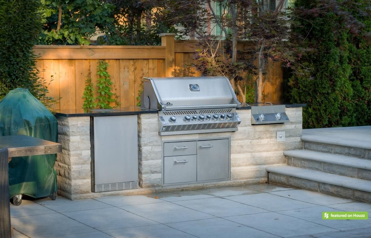 this custom bbq station is clad in natural stone and features a