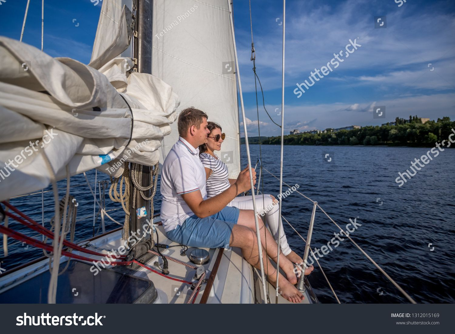Two Young People Man And Woman Sitting On The Yacht Board And