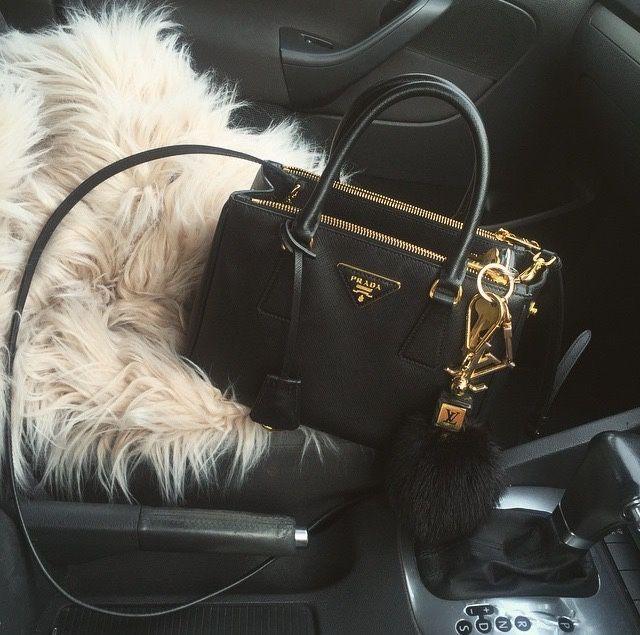 Black Prada crossbody handbag with Louis Vuitton fluffy charm and beige fur sitting shotgun in black car